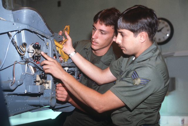 SENIOR AIRMAN Manuel Topete (foreground) and AIRMAN Timothy M. Garczynski, aerospace physiology specialists, inspect a malfunctioning trigger of an ejection seat trainer