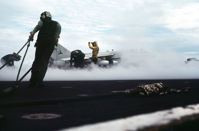 Steam from a catapult partially obscures an A-7 Corsair II aircraft preparing for takeoff on the flight deck of the aircraft carrier USS MIDWAY (CV41)