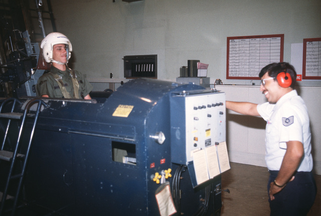 Technical Sergeant Santos Navarette (right) and AIRMAN Timothy M. Garczynski, aerospace physiology specialists, test an ejection seat trainer after a malfunctioning trigger has been repaired