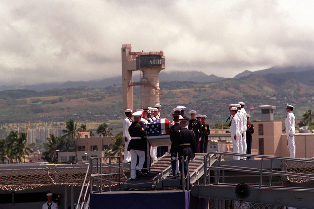 Upon completion of ceremonies, the flag draped casket of the Unknown Soldier of the Vietnam War is carried aboard the frigate USS BREWTON (FF 1086) by a joint service honor guard. The casket will be transported to Alameda, California, and then transferred to its final destination at the Tomb of the Unknown Soldier, Arlington National Cemetery, Virginia