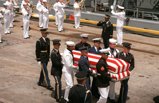 A joint services casket team carries the casket of the Unknown Serviceman of the Vietnam Era from the frigate USS BREWTON (FF 1086) to a waiting hearse. The Unknown will be taken to Travis Air Force Base, California, and then flown to Washington, District of Columbia. He will be interred at the Tomb of the Unknowns in Arlington National Cemetery on Memorial Day, May 28, 1984