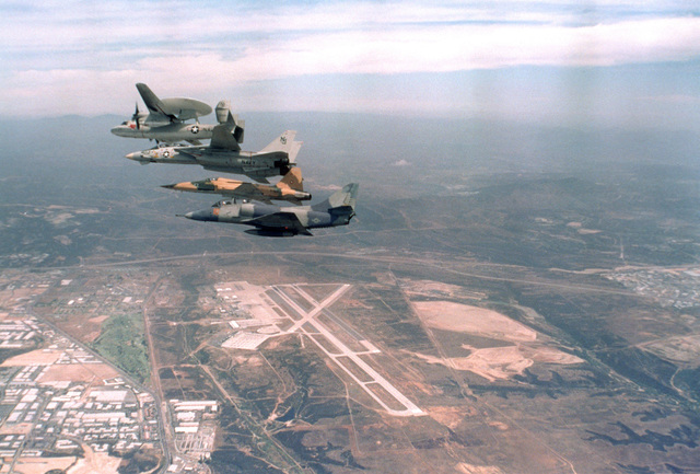 An air-to-air left side view, top to bottom, of an E-2 Hawkeye aircraft from Airborne Early Warning Squadron 110 (VAW-110), F-14A Tomcat aircraft from Fighter Squadron 124 (VF-124), F-5E Tiger II aircraft from Navy Fighter Weapons School, and a TA-4J Skyhawk aircraft from Fighter Squadron 126 (VF-126)