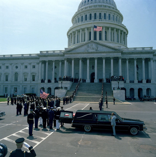A joint services casket team removes the casket of the Unknown Serviceman of the Vietnam Era from a hearse parked outside the east entrance of the Capitol. The casket will be carried past the color guard and joint services honor condon lining the steps of the Capitol and placed in the rotunda, where the Unknown will lie in state until Memorial Day