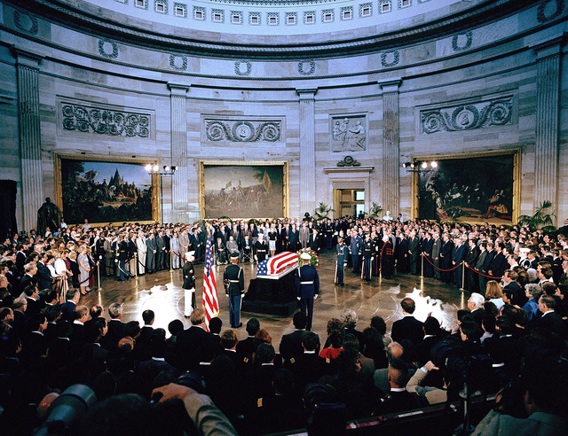 Members of a joint services honor guard stand by as members of a joint services casket team place the casket of the Unknown Serviceman of the Vietnam Era on a catafalque in the Capitol rotunda. President and Mrs. Ronald Reagan, VIPs, Vietnam veterans and other guests are attending the ceremony. The Unknown will lie in state in the rotunda until Memorial Day