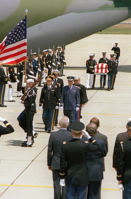 Preceded by a joint services color guard and members of the clergy, a joint services casket team carries the casket of the Unknown Serviceman of the Vietnam Era past a joint services honor cordon during the arrival ceremony on the flight line. The Unknown was brought from Travis Air Force Base, California, to Andrews aboard the C-141B Starlifter aircraft in the background