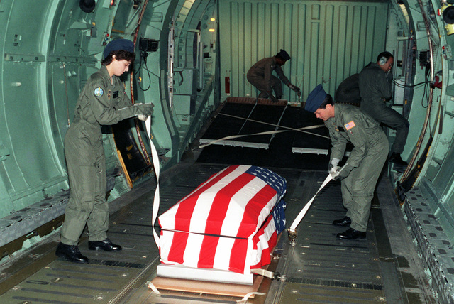 Technical Sergeant Gary D. Yoder, 708th Military Airlift Squadron, and AIRMAN 1ST Class Naomi J. Williams, 7th Military Airlift Squadron, both loadmasters, secure the casket of the Unknown Serviceman of the Vietnam Era aboard a C-141B Starlifter aircraft for the flight to Andrews Air Force Base, Maryland. The Unknown will be transferred from Andrews to the Capitol to lie in state