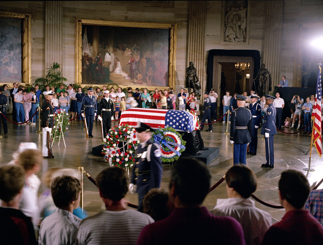 Visitors gather around the casket of the Unknown Serviceman of the Vietnam Era as he lies in state in the Capitol rotunda. The is attended by a joint services honor guard