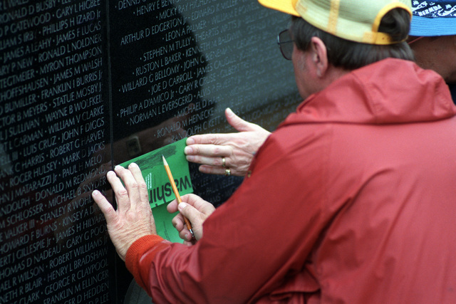A visitor takes a pencil rubbing of one of the names on the face of the Vietnam Veterans Memorial on the day of the state funeral service for the Unknown Serviceman of the Vietnam Era