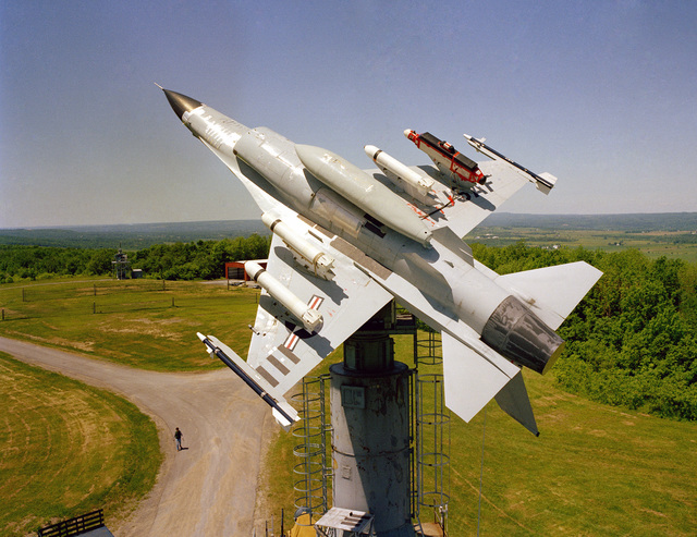 An F-16A Fighting Falcon aircraft on a test stand at the Newport Test Site of the Rome Air Development Center. The plane is armed with AIM-9 Sidewinder missiles on the wing tips, three Rockeye II Mark 20 cluster bombs on the wing pylons, and an AN/ALQ-119 electronic countermeasures pod on an outside wing pylon