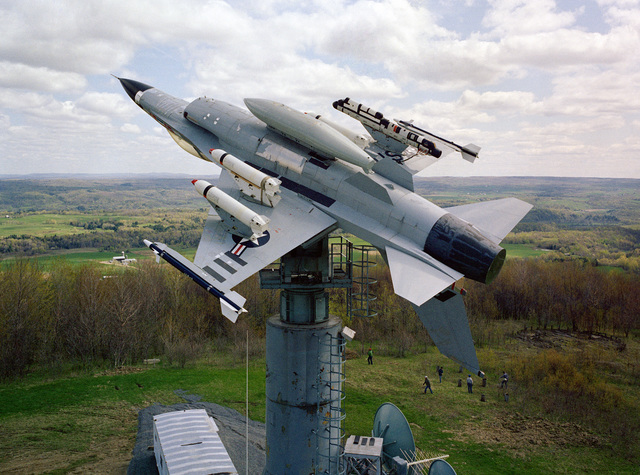 An F-16A Fighting Falcon aircraft on a test stand at the Newport Test Site of the Rome Air Development Center. The plane is armed with AIM-9 Sidewinder missiles on the wing tips, three Mark 20 Rockeye II cluster bombs on the wing pylons, and an AN/ALQ-119 electronic countermeasures pod on an outside wing pylon