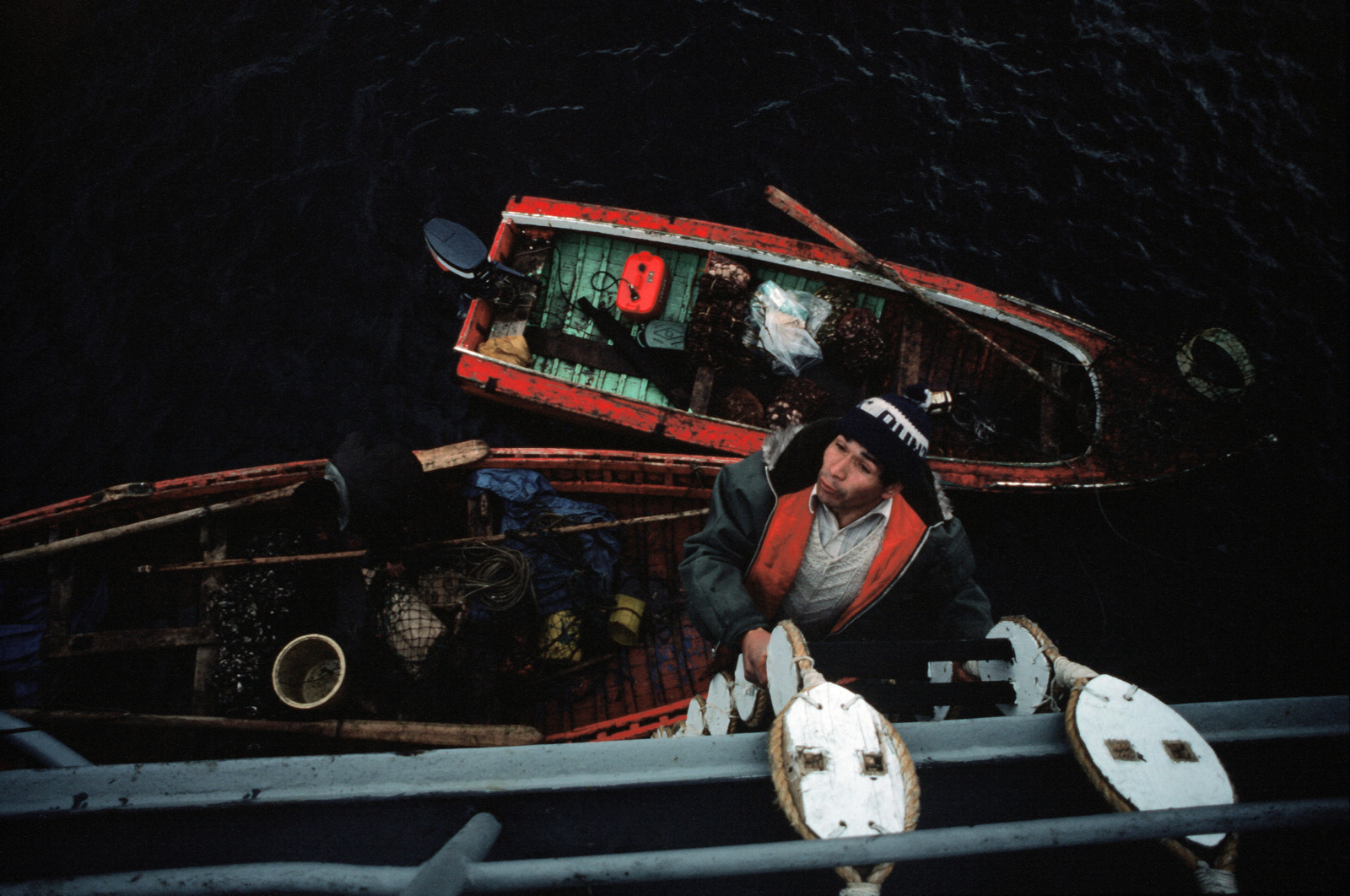 A Chilean fisherman climbs a ladder to go aboard the destroyer USS THORN (DD 988) to sell seafood to the crewman while the ship is stopped briefly in the inland waterway during Operation UNITAS XXV