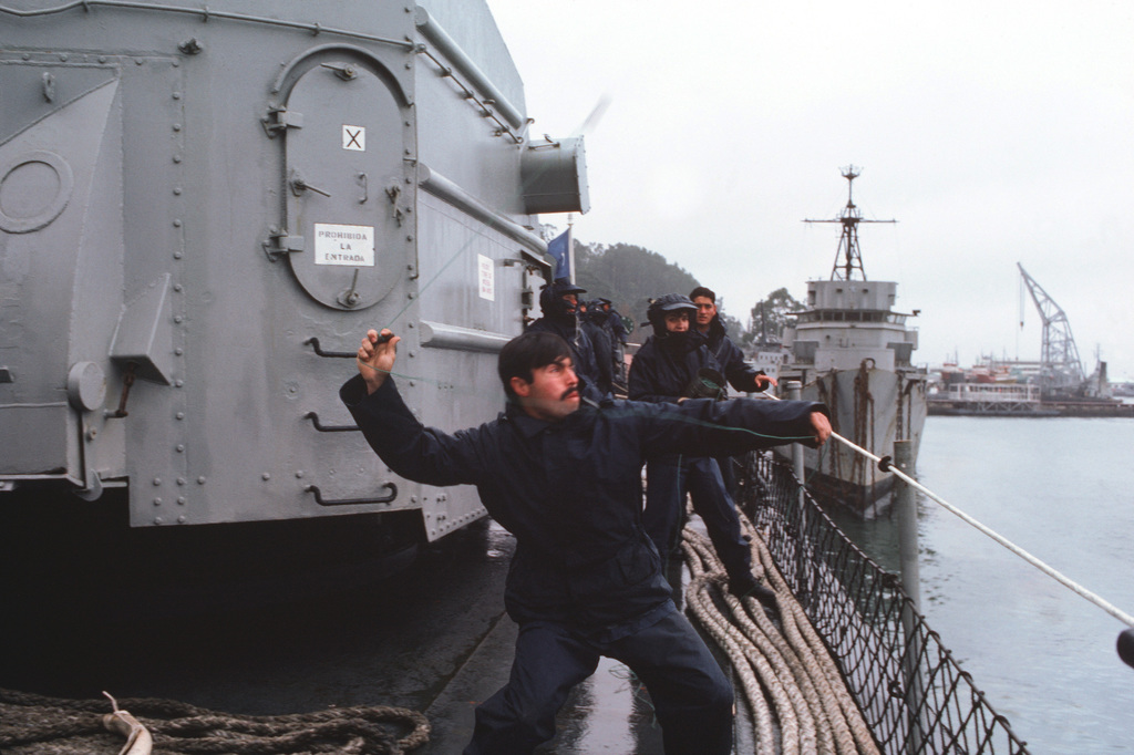 A Chilean seaman hurls a line ashore from the frigate ALMIRANTE LYNCH (PFG 07) as the flagship arrives in the port of Talchuano during Operation UNITAS XXV
