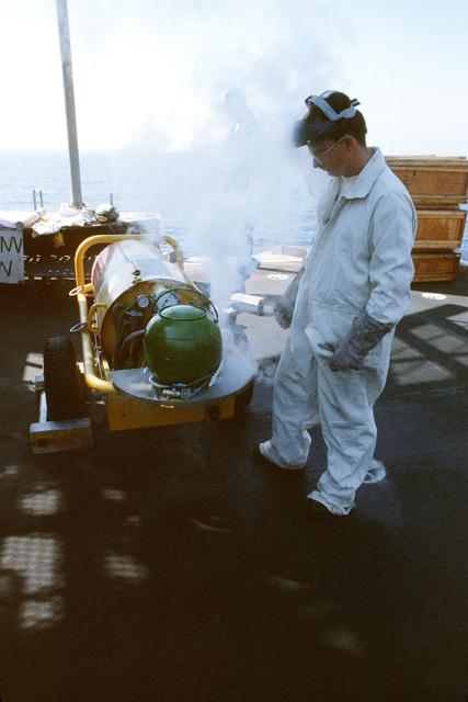 A crew member aboard the aircraft carrier USS JOHN F. KENNEDY (CV 67) fills storage bottles with liquid breathing oxygen