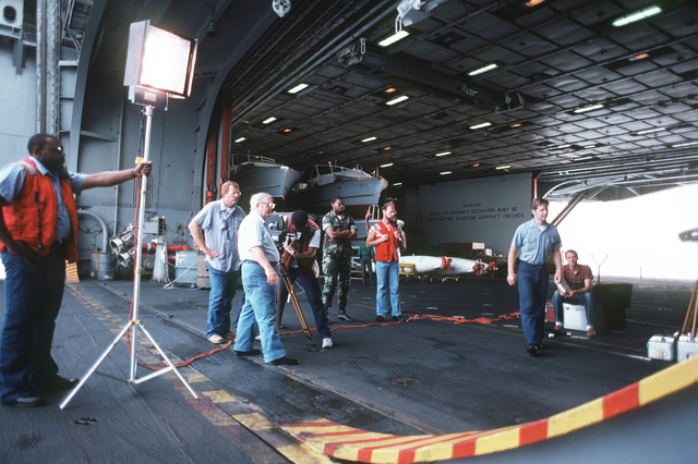 A motion picture crew from the Naval Audiovisual Center (NAVC), Washington, District of Columbia films activities aboard the aircraft carrier USS JOHN F. KENNEDY (CV 67). Mr. Thomas Garvey, (left foreground) Division Head, Motion Media Department, NAVC, stands by the camera crew as supervisor