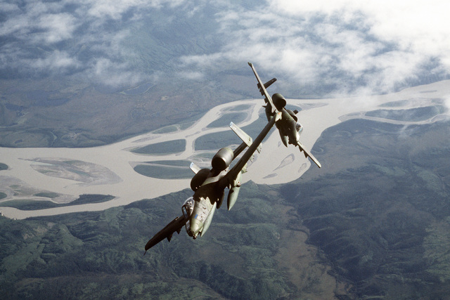 Air to air front view of two A-10 Thunderbolt aircraft of the 18th Tactical Fighter Wing, Eielson Air Force Base, Alaska, breaking from formation during flight operations