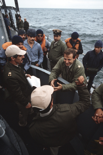 Lieutenant Horacio Sassi, center, discusses a successful gunnery exercise with the gun crew aboard the Uruguayan frigate 18 DE JULIO (3) during Operation UNITAS XXV