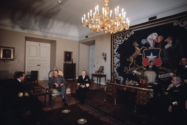 President of the Republic of Chile General Augusto Pinochet, center, discusses UNITAS with Rear Admiral Clinton Taylor, UNITAS XXV task force commander, and Admiral Jose T. Merino Castro, Commander In CHIEF of the Chilean navy