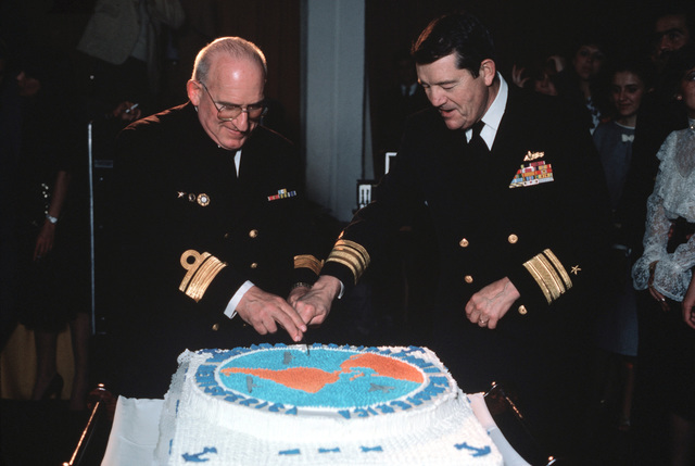 Rear Admiral Clinton Taylor, right, UNITAS XXV task force commander, and Rear Admiral Jorge Labarde, Uruguayan chief of sea forces, cut a cake at a reception to mark the silver anniversary of UNITAS