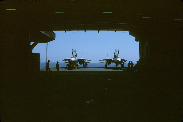 Two F-14 Tomcat fighter aircraft parked on the flight deck of the aircraft carrier USS JOHN F. KENNEDY (CV 67) as seen from the inside of the hangar bay