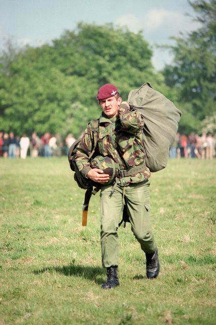 A British paratrooper carries his gear off the landing zone after a re-enactment of a World War II parachute jump on the 40th anniversary of D-day, the invasion of Europe