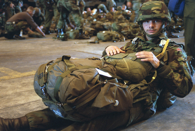 A British paratrooper sits on the floor with his gear before a jump. He is participating in a ceremony commemorating the 40th anniversary of D-Day, the invasion of Europe