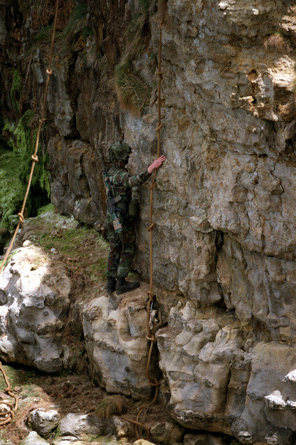 A member of the 2nd Ranger Battalion, U.S. Army, participates in the re-enactment of a cliff climb made by members of the same unit on D-day, World War II. The re-enactment is part of a ceremony commemorating the 40th anniversary of D-day, the invasion of Europe