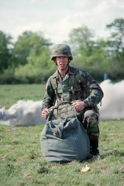 A member of the 82nd Airborne Division gathers his gear after a re-enactment of a World War II parachute jump on the 40th anniversary of D-day, the invasion of Europe