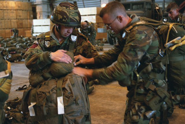 A member of the 82nd Airborne Division helps a British paratrooper strap on his parachute before a jump. They are participating in a ceremony commemorating the 40th anniversary of D-Day, the invasion of Europe