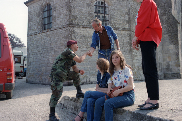 A member of the 82nd Airborne Division talks with local civilians on the 40th anniversary of D-day, the invasion of Europe