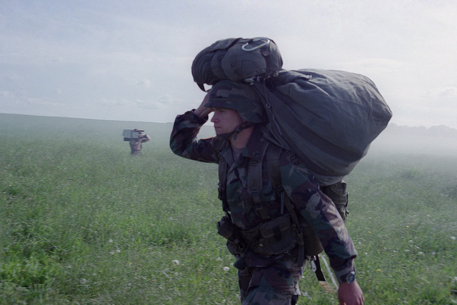 A paratrooper of the 82nd Airborne Division carries his parachute after a jump during the 40th anniversary celebration of D-Day, the invasion of Europe