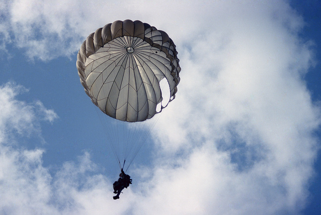 A paratrooper participates in a re-enactment of a World War II parachute jump on the 40th anniversary of D-day, the invasion of Europe