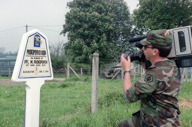 A photojournalist videotapes a war memorial on the 40th anniversary of D-day, the invasion of Europe
