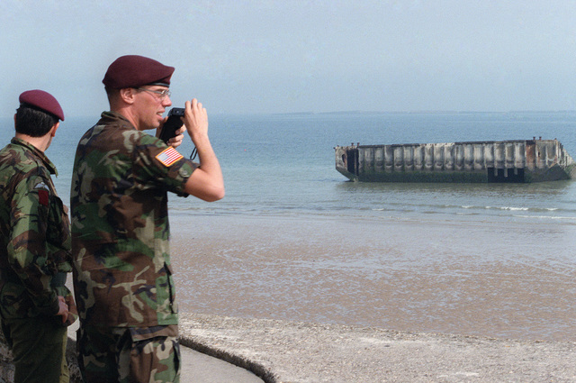 A soldier of the 82nd Airborne Division photographs a sunken World War II barge on the 40th anniversary of D-day, the invasion of Europe