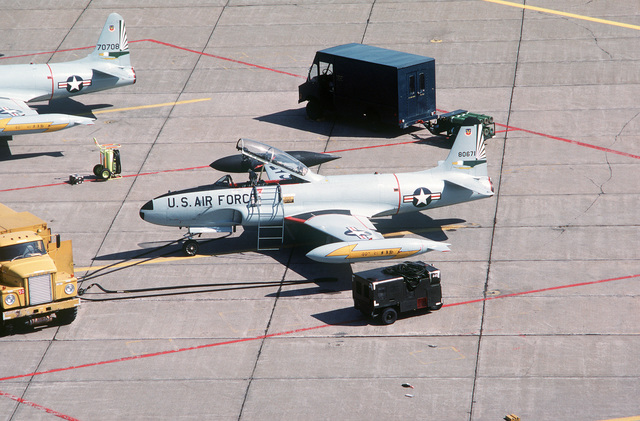 An elevated left side view of a T-33 Shooting Star aircraft from the 49th Fighter Interceptor Squadron being refueled from a tanker truck on the flight line