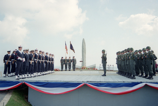French and American servicemen stand at attention as a color guard parades the colors at a World War II memorial on the 40th anniversary of D-day, the invasion of Europe