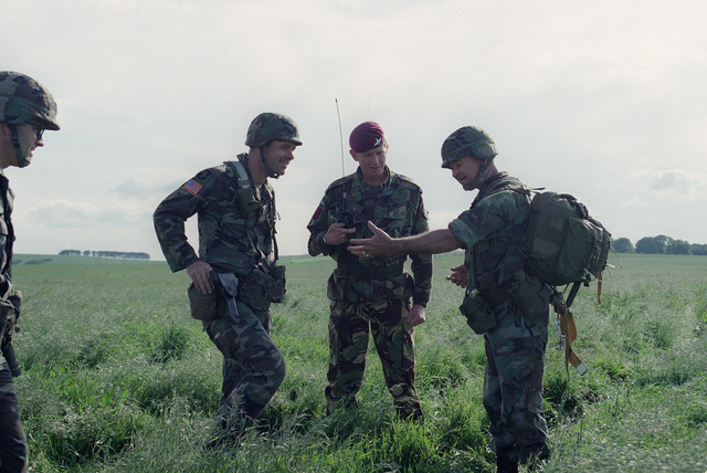 Major General (MGEN) Edward L. Trobaugh, commander, 82nd Airborne Division, right speaks with Lieutenant Colonel Jackson, commander of the 1ST British Parachute Regiment, center, after a parachute jump on the 40th anniversary of D-day, the invasion of Europe