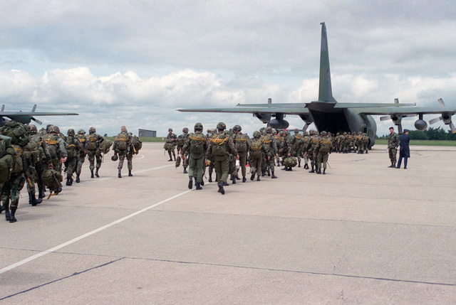 Members of the 82nd Airborne Division and British paratroopers board a C-130E Hercules aircraft prior to a jump. They are participating in a ceremony commemorating the 40th anniversary of D-Day, the invasion of Europe