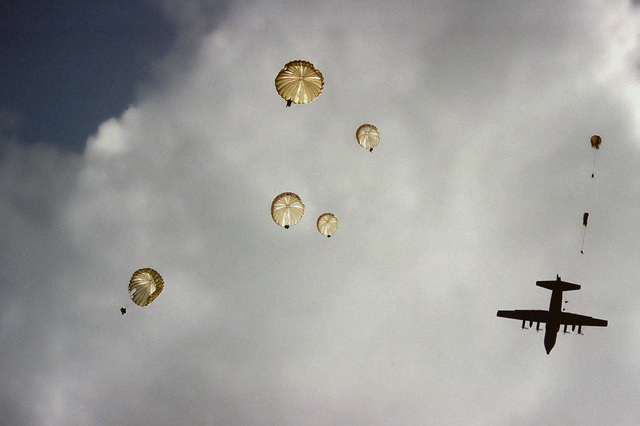 Members of the 82nd Airborne Division and British paratroopers jump from a C-130E Hercules aircraft during a re-enactment of a World War II parachute jump on the 40th anniversary of D-day, the invasion of Europe