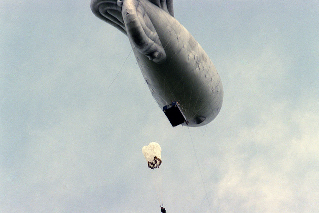 Members of the 82nd Airborne Division and British paratroopers jump from a platform suspended under a balloon while practicing for a jump into Sainte-Mere-Eglise, France, on the 40th anniversary of D-day, the invasion of Europe