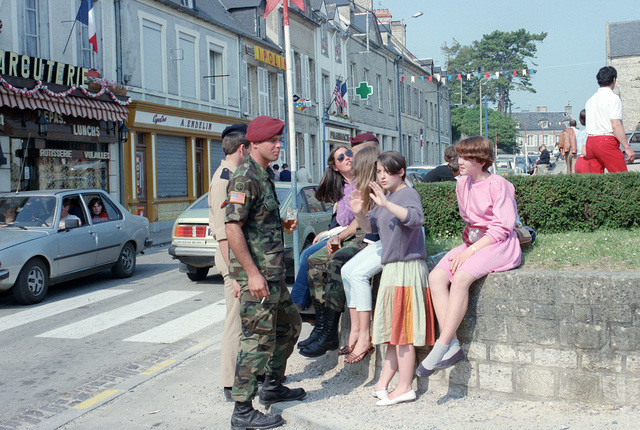 Members of the US 82nd Airborne Division speak with local villagers on the 40th anniversary of D-day, the invasion of Europe