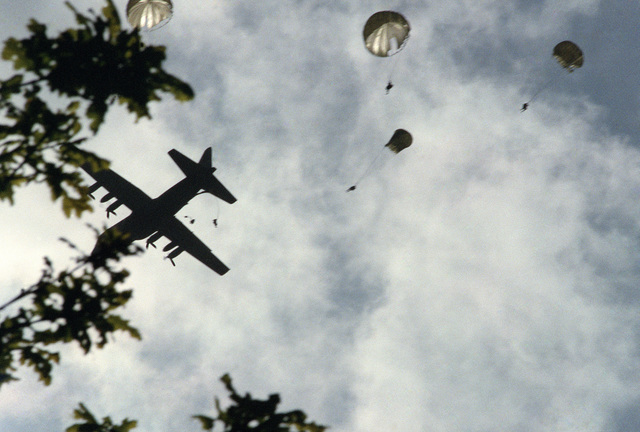 Paratroopers of the 82nd Airborne Division jump from a C-130E Hercules aircraft during a re-enactment of a World War II parachute jump on the 40th anniversary of D-day, the invasion of Europe