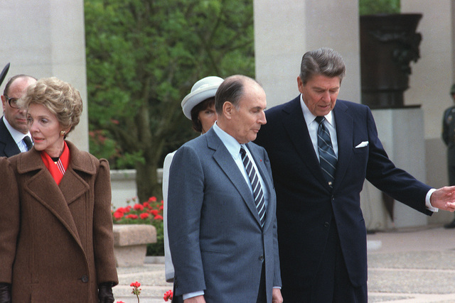 President Ronald Reagan speaks with President Mitterrand of France during a wreath-laying ceremony at the American cemetery at Omaha Beach on the 40th anniversary of D-day, the invasion of Europe. To the left stands Mrs. Reagan and in the background is Mrs. Mitterrand
