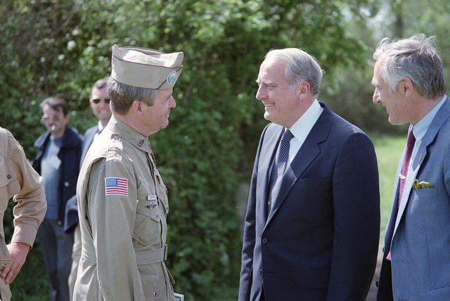 Secretary of the Army John O. Marsh, center, speaks with retired Colonel (COL) Bob Piper during a ceremony commemorating the 40th anniversary of D-day, the invasion of Europe