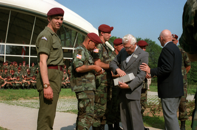 Soldiers of the 82nd Airborne Division receive commemorative key chains from World War II veterans on the 40th anniversary of D-day, the invasion of Europe