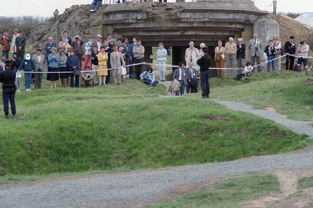 Spectators standing in front of the ruins of a fortification listen to an address during a ceremony commemorating the 40th anniversary of D-Day, the invasion of Europe