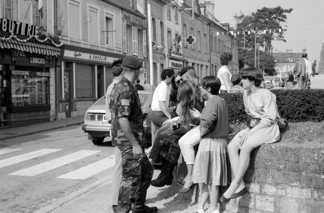 Members of the 82nd Airborne Divison talk with local residents while touring the town. They are in France to participate in the 40th anniversary celebration of D-day, the invasion of Europe
