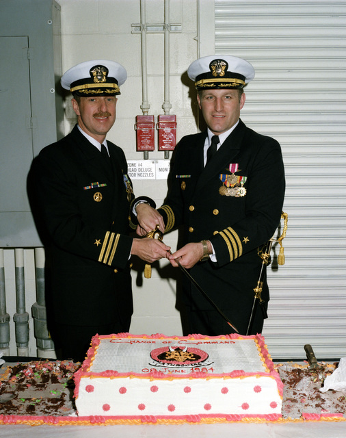 Commander (CDR) Harry A. Jupin, left, and CDR Kenneth L. Pyle cut a cake during the Change of Command Ceremony for Attack Squadron 196 (VA-196). CDR Jupin is relieving CDR Pyle as Commanding Officer of VA-196