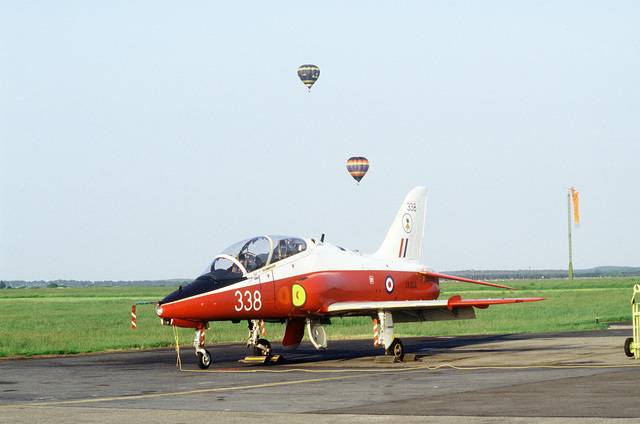A BAe Hawk aircraft parked on the flight line during Air Fete '84. Two hot air balloons are in the background