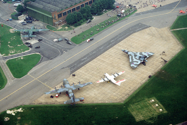 An aerial view, from left to right, of a Royal Air Force C. Mark 1 Hercules aircraft, a Canadian CC-132 Dash 7 aircraft and a Royal Air Force Vulcan aircraft parked on the flight line during Air Fete '84