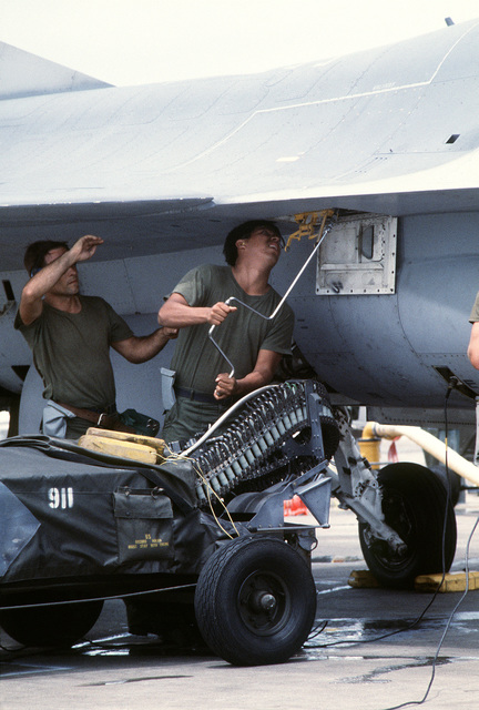 Personnel assigned to the 56th Equipment Maintenance Squadron, load 20mm rounds into an M61A1 20mm multibarrel cannon mounted in the fuselage of an F-16 Fighting Falcon fighter aircraft. They are participating in the June Air Defense exercise